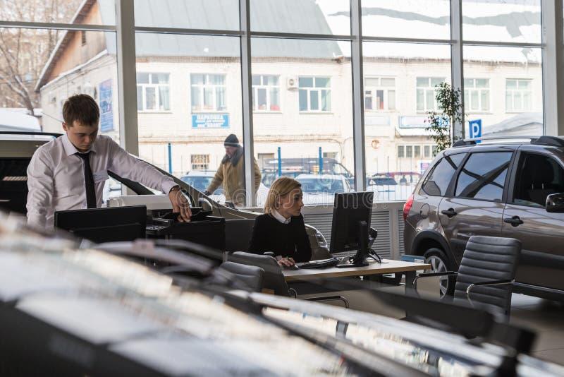 Car and manager in showroom of dealership AVTOVAZ named SeverAvto in Kirov city in 2018. Top view. Kirov, Russia - March 06, 2018: Cars and manager in showroom stock image