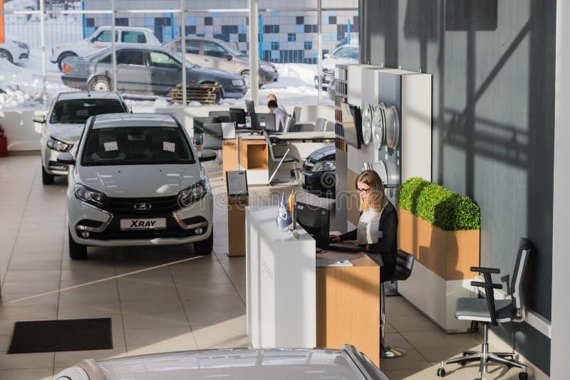 Car and manager in showroom of dealership AVTOVAZ named SeverAvto in Kirov city in 2018. Top view. Kirov, Russia - March 06, 2018: Cars and manager in showroom royalty free stock photos