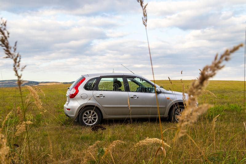 Car in the meadow and clouds in the sky on a summer or autumn. Car in the meadow and clouds in the sky in a summer or an autumn day royalty free stock photography