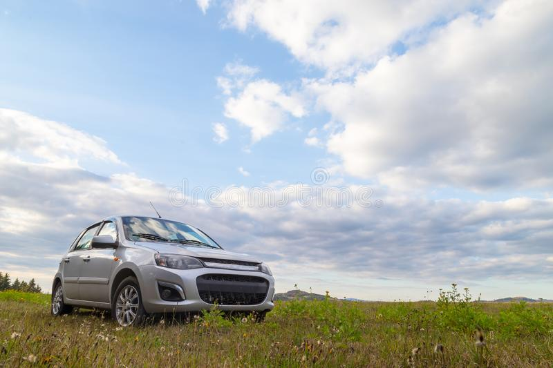 Car in the meadow and clouds in the sky on a summer or autumn. Car in the meadow and clouds in the sky in a summer or an autumn day stock image