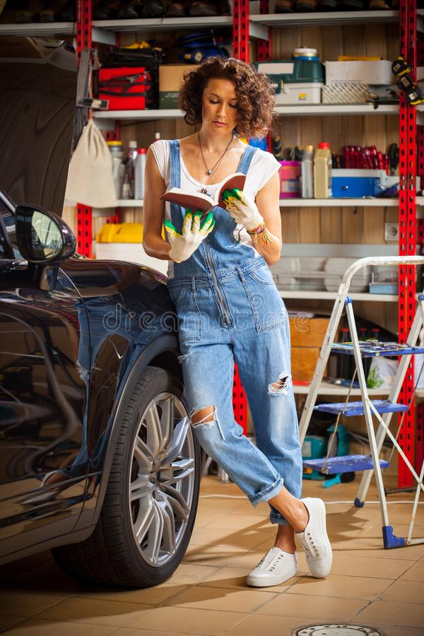 Car mechanic, woman studying the instructions for repair and adjustment of the car. Preparing for autotravel. royalty free stock photo