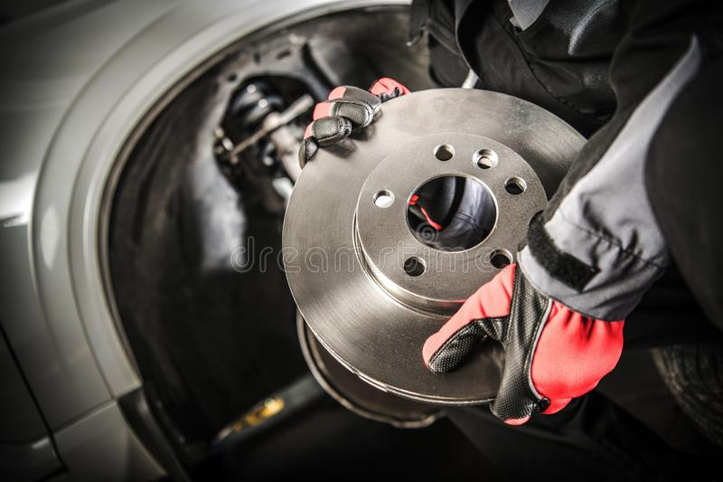 Car Mechanic with Brake Disc. Car Mechanic with Modern Vehicle Brake Disc in Hands. Automotive Theme stock photography