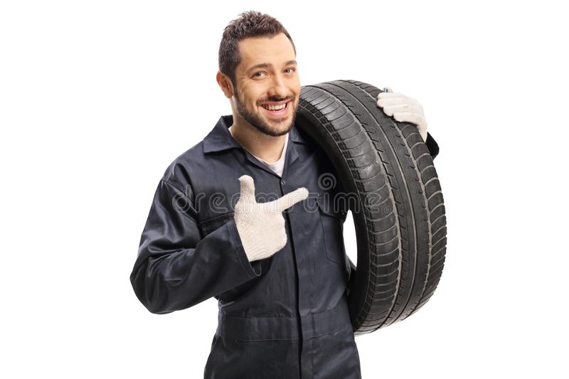 Car mechanic carrying a tire and pointing. Isolated on white background royalty free stock image