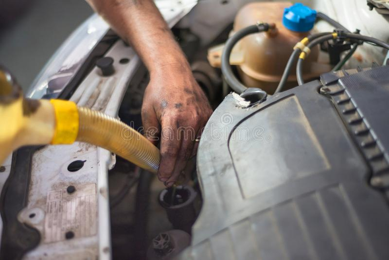Car mechanic changing engine oil in a dirty engine. royalty free stock images