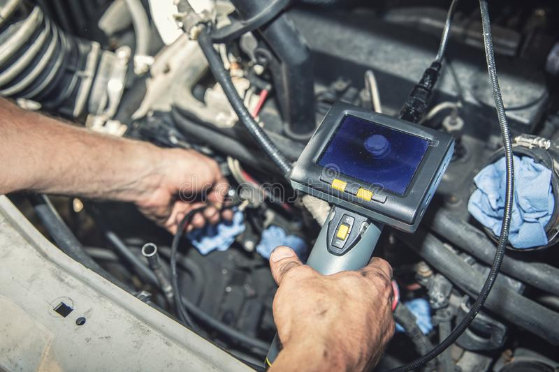 Car mechanic check the vehicle engine with borescope stock image