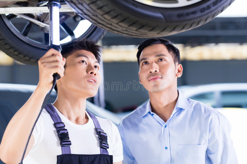 Car mechanic and customer in Asian auto workshop. Asian Chinese car mechanic with customer looking at auto floor with lamp stock photography