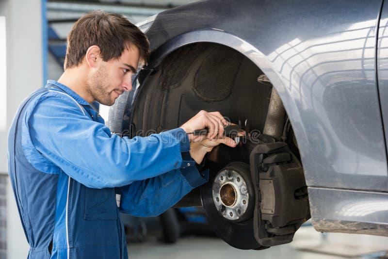 Car Mechanic Examining Brake Disc With Caliper. Male car mechanic examining brake disc with caliper in garage stock image