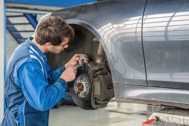 Car Mechanic Examining Brake Disc With Caliper. Young male car mechanic examining brake disc with caliper in garage stock photos