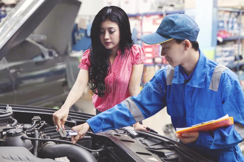 Car mechanic helping a customer fixing the car while holding a checklist royalty free stock images