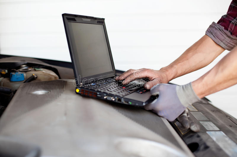 Car mechanic with laptop. Checking enine stock photos
