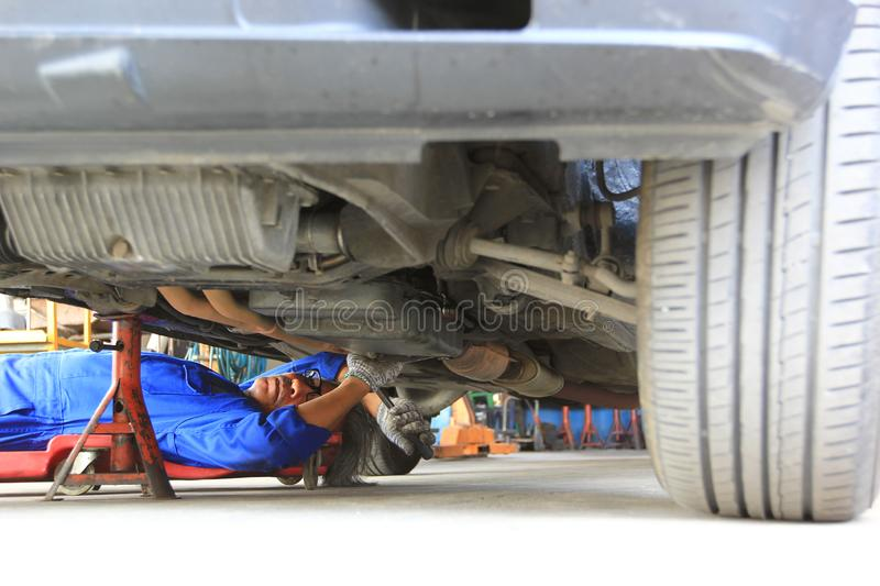 Car mechanic lying down and working under car in auto repair service royalty free stock photography