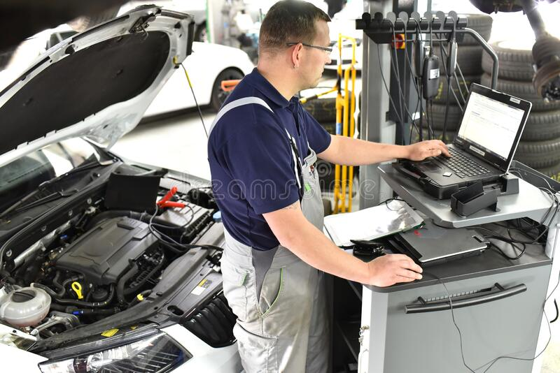 Car mechanic maintains a vehicle with the help of a diagnostic computer - modern technology in the car repair shop. Closeup photo stock photos