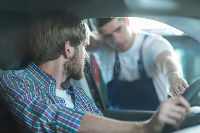 Car mechanic and male driver. Picture of young car mechanic and male driver stock photo