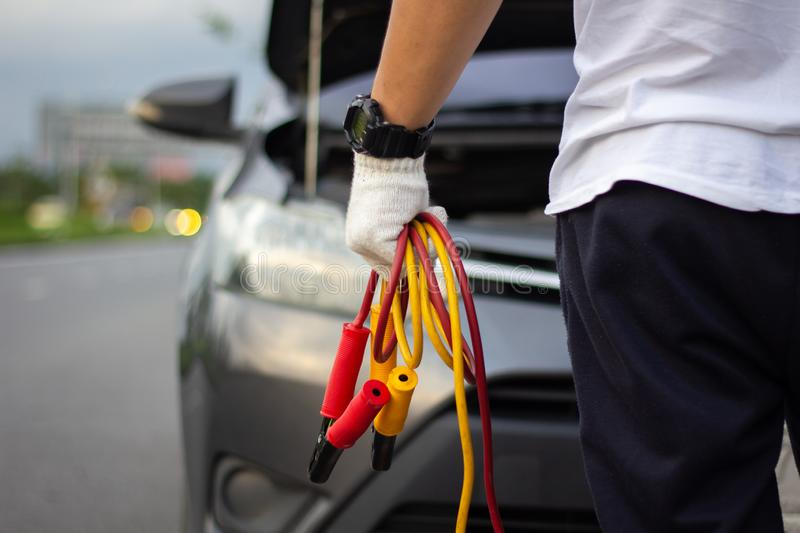 Car mechanic man holding battery jumper cables to charge a dead. Battery. Close up hand charging car battery with electricity red and yellow jumper cables. Car stock image