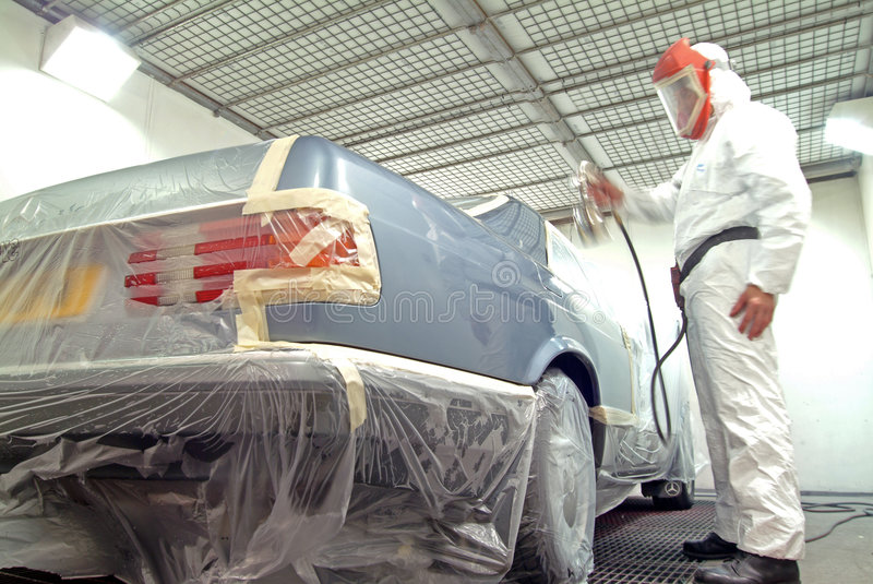 Car mechanic and paint spray royalty free stock photography