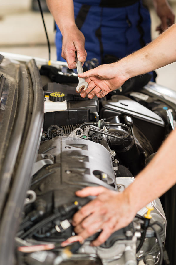 Car mechanic passing a wrench to colleague. Passing a wrench to co-worker car mechanic stock image