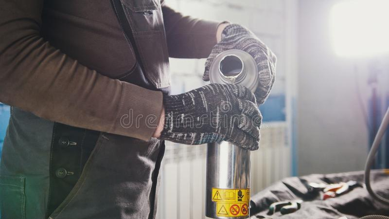 Car mechanic pours motor oil for car at repair service station stock photos