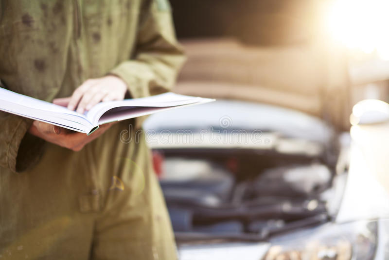 Car mechanic reading instructions. Mechanic reading instructions manual and replacing broken part stock images