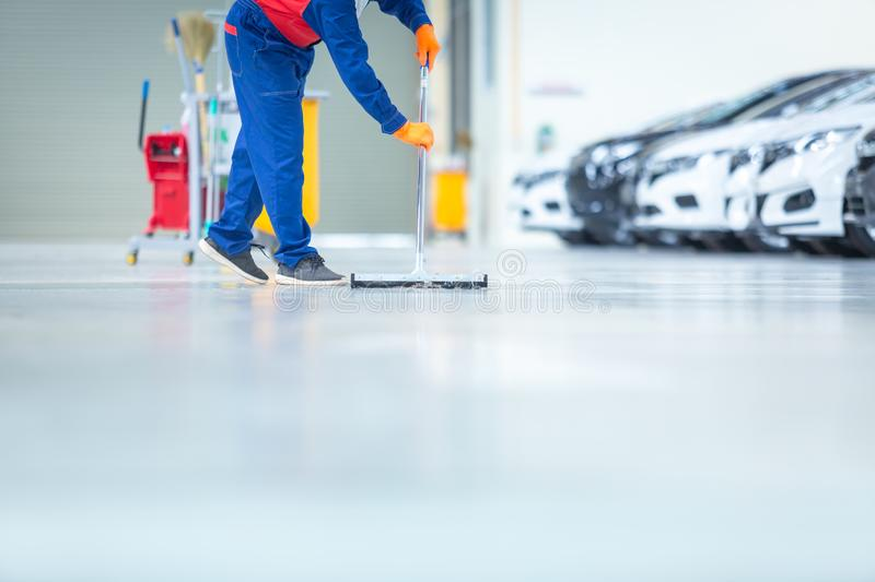 Car mechanic repair service center cleaning using mops to roll water from the epoxy floor. In the car repair service center.  royalty free stock photo