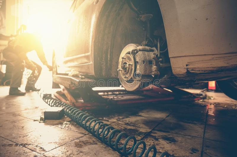 Car mechanic replace car wheels of lifted automobile by pneumatic wrench at repair service shop garage station, sunlight effect. Toned royalty free stock photos