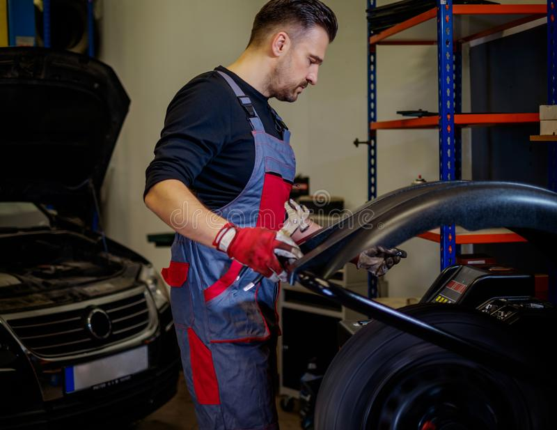 Car mechanic mounts tire on wheel in a workshop stock image