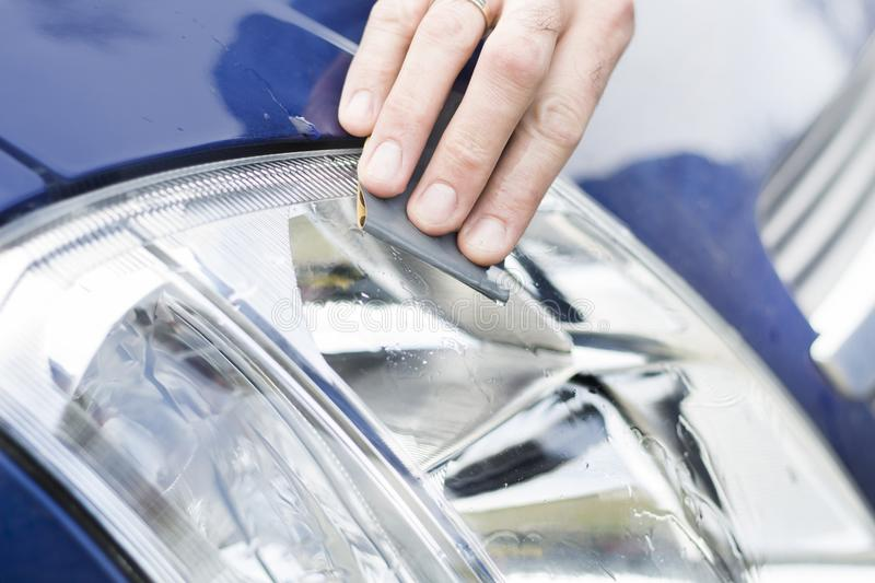The car mechanic`s hand polishes with sandpaper and water frosted reflector glass. Refinish the headlights. Polished matt glass headlight with sand paper and royalty free stock photography