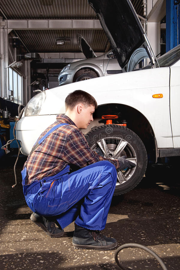 Car mechanic screwing or unscrewing car wheel of lifted automobile by pneumatic wrench. At repair service station stock photos