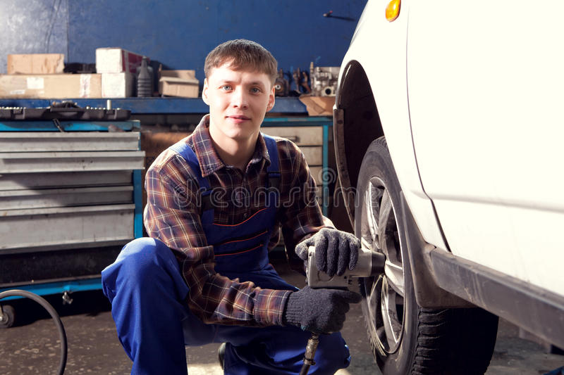 Car mechanic screwing or unscrewing car wheel of lifted automobile by pneumatic wrench. At repair service station royalty free stock image