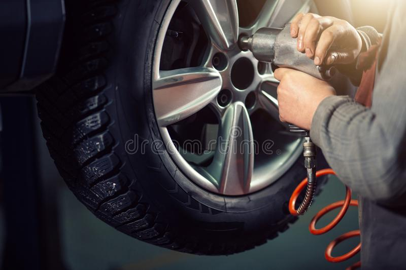 Mechanic screwing or unscrewing car wheel by pneumatic wrench. Car mechanic screwing or unscrewing car wheel by pneumatic wrench royalty free stock photos
