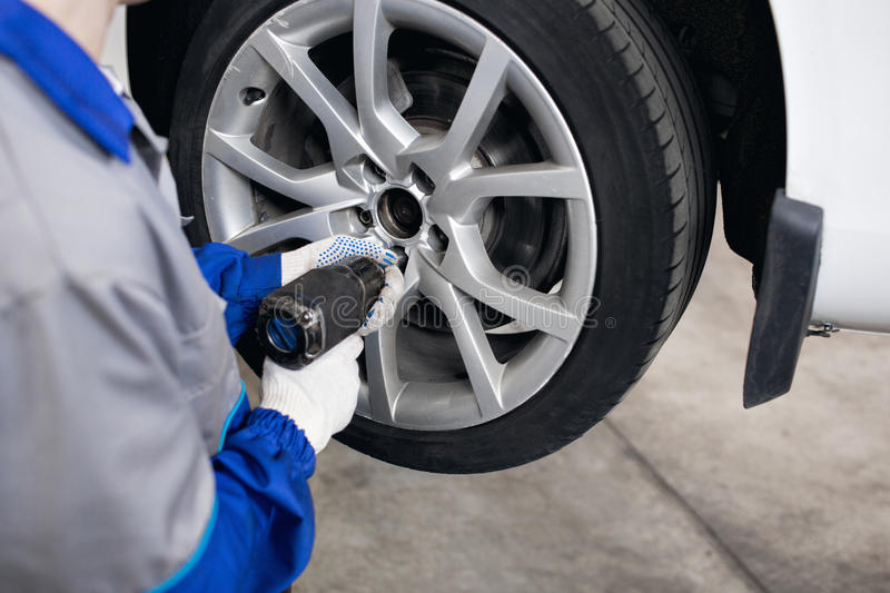 Car mechanic screwing or unscrewing wheel of lifted automobile by pneumatic wrench at repair service station. Car mechanic screwing or unscrewing car wheel of stock photos