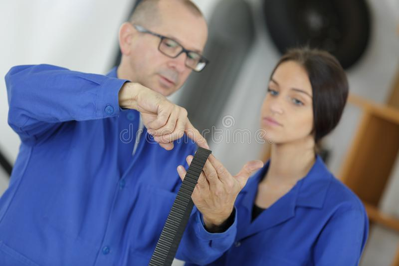 Car mechanic showing female apprentice timing belt stock photo