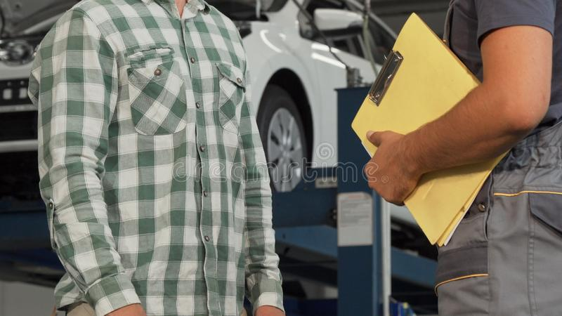 Car mechanic talking to the customer at the garage stock image