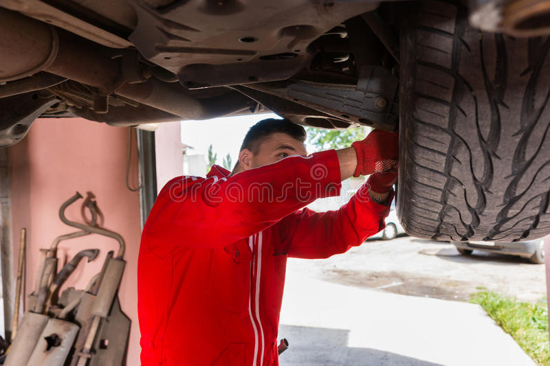 Car mechanic in uniform is repairing wheel while working underneath a lifted car. With working equipment for diagnostic in auto repair service stock image