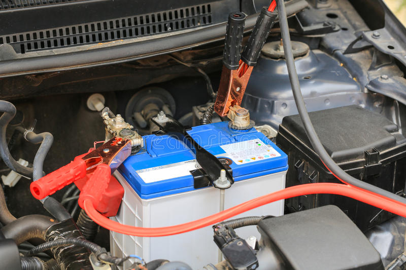 Car mechanic uses battery jumper cables charge a dead battery. stock photography