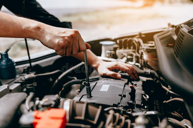 The car mechanic uses a wrench to open the car`s engine box stock photo