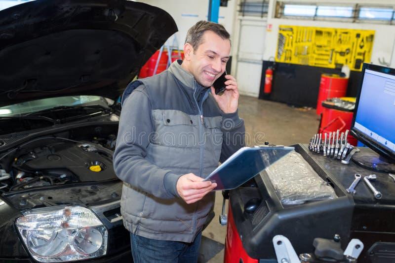 Car mechanic using telephone royalty free stock photos