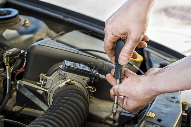 Car mechanic at work. Car mechanic working under the engine hood of a car royalty free stock photography
