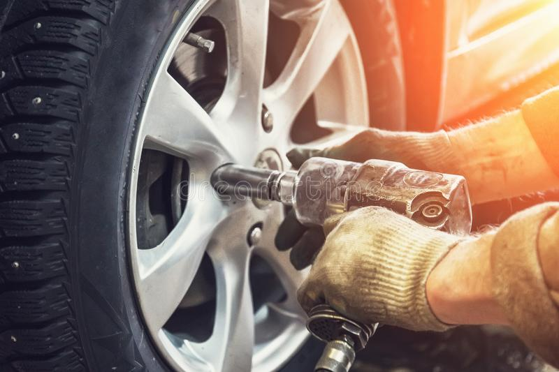 Car mechanic worker doing tire or wheel replacement with pneumatic wrench in garage of repair service station. Sunlight effect, toned stock photos