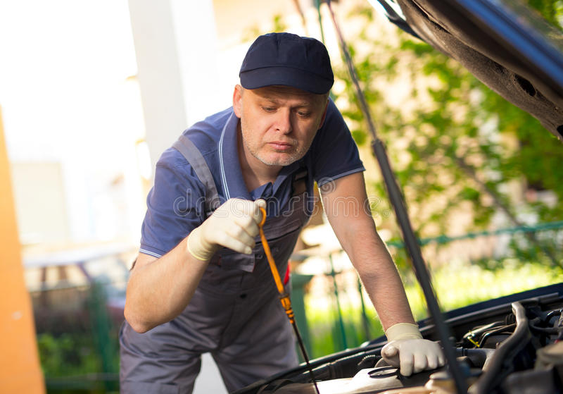 Car mechanic working in auto repair service. Mechanic working in auto repair service royalty free stock photo