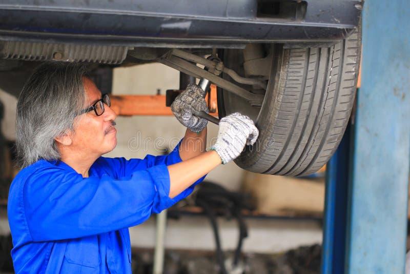 Car mechanic working under car in auto repair service stock photo