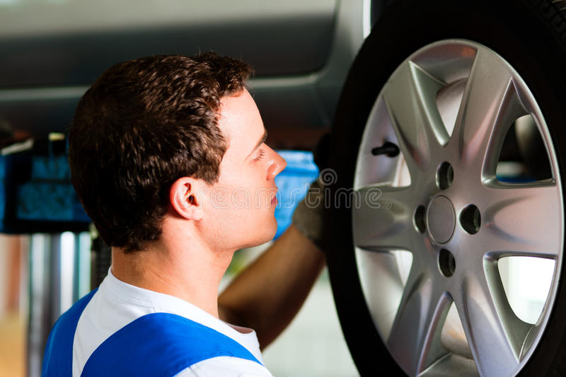Download Car Mechanic In Workshop Changing Tire Stock Image - Image: 17917111