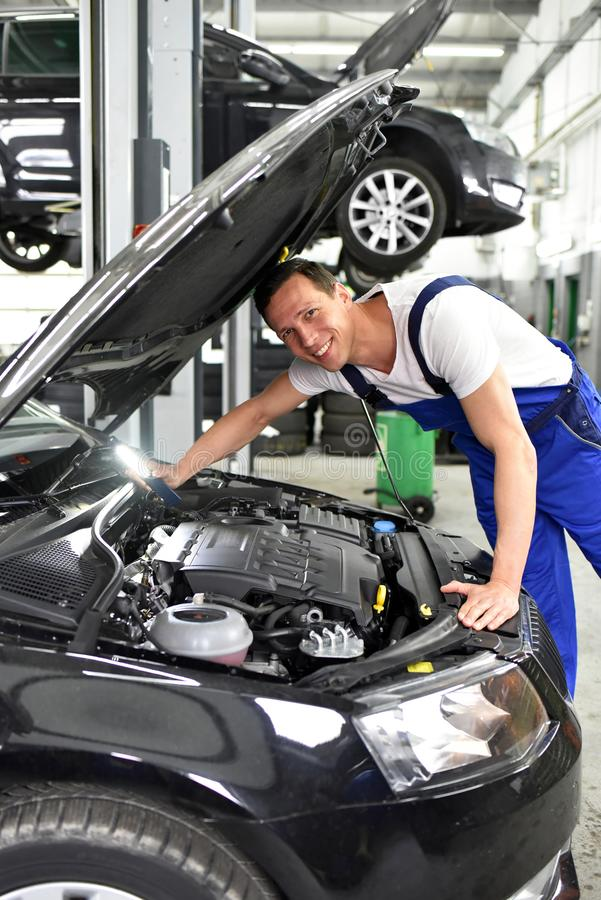 car mechanic in a workshop - engine repair and diagnosis on a vehicle royalty free stock photo