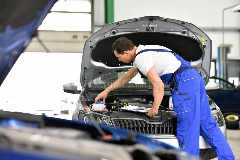 car mechanic in a workshop - engine repair and diagnosis on a vehicle stock photography