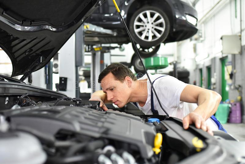 car mechanic in a workshop - engine repair and diagnosis on a vehicle royalty free stock photos