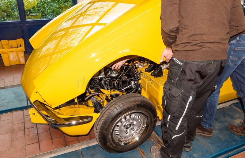 Car mechanics align the bonnet correctly when assembling - Serie Repair Workshop.  royalty free stock photo