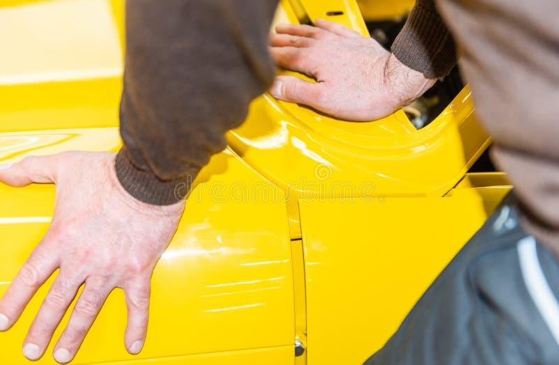 Car mechanics align the bonnet correctly when assembling - Serie Repair Workshop.  royalty free stock images