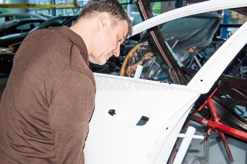 Car mechanics align the bonnet correctly when assembling - Serie Repair Workshop.  royalty free stock photography