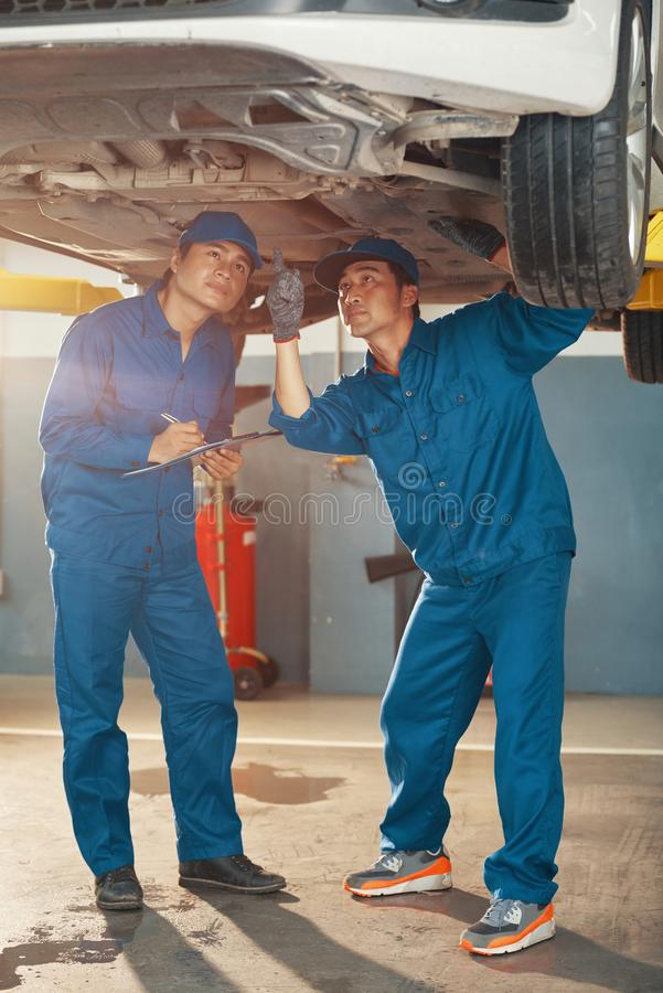 Car mechanics inspecting problems royalty free stock images