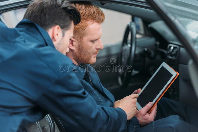 Car mechanics using digital tablet. Two car mechanics sitting in a car at workshop using a digital tablet royalty free stock photography
