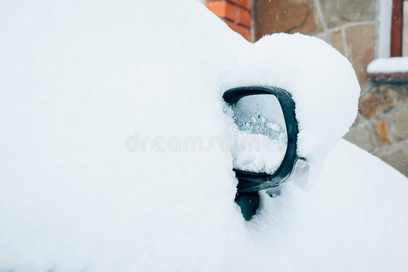 Car mirror in snow. Frozen, snow covered passenger car mirror royalty free stock images